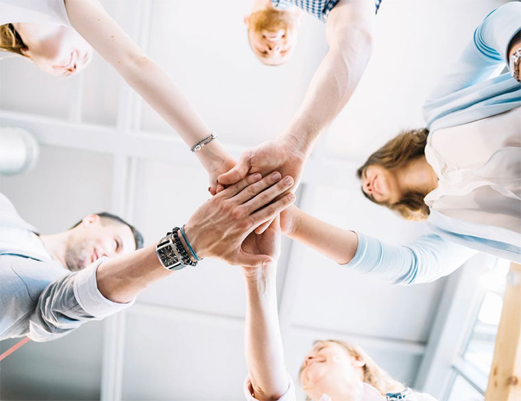 Five coworkers with hands meeting in middle. View from below.